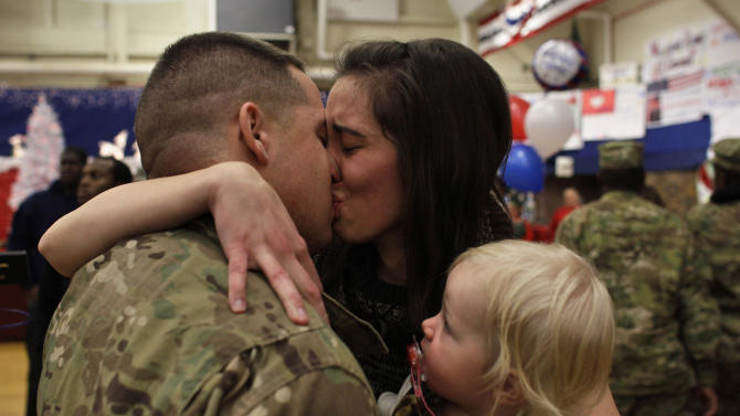 In this Nov. 30, 2012. photo, U.S. Army 1st Lt. Aaron Dunn kisses his wife Leanne, holding their baby Emma, age 14 months, as they reunite during an arrival ceremony for soldiers returning from a deployment in Afghanistan, at Ft. Carson, in Colorado Springs, Colo. 1st Lt. Dunn, with the 4th Brigade Combat Team, 4th Infantry Division, had not seen his wife and baby since he deployed in March. (AP Photo/Brennan Linsley)