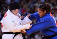 Saudi Arabia's Wojdan Shaherkani (white) competes with Puerto Rico's Melissa Mojica (blue) during their women's +78kg judo contest match of the London 2012 Olympic Games on August 3, 2012 at the ExCel arena in London. AFP PHOTO / EMMANUEL DUNAND