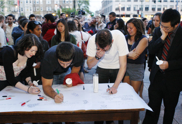 Boston University students gather to sign a condolence note prior to a candlelight vigil on Marsh Plaza at Boston University, Saturday, May 12, 2012, in Boston, for three students studying in New Zeal
