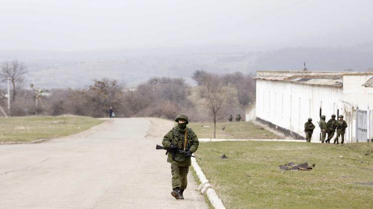 Armed men, believed to be Russian servicemen, are seen outside a Ukrainian military unit in the village of Perevalnoye outside Simferopol