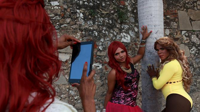 Revellers take pictures during a gay pride parade in Santo Domingo