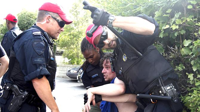 Police detain a protestor prior to a rally for Canadian Prime Minister Harper in Montreal