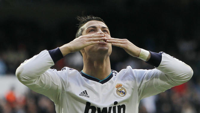 Real Madrid's Cristiano Ronaldo, from Portugal, blows kisses after scoring a goal during a Spanish La Liga soccer match against Levante at the Santiago Bernabeu stadium in Madrid, Spain, Saturday, April 6, 2013. (AP Photo/Andres Kudacki)
