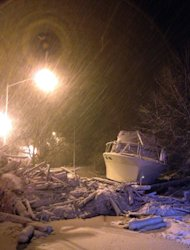 In this photo provided by Tom DeVito, a boat that washed ashore during Superstorm Sandy sits covered in snow on Hylan Blvd. in the Staten Island borough of New York as a nor&#39;easter hits the city, Wednesday, Nov. 7, 2012. A nor&#39;easter blustered into New York and New Jersey on Wednesday with rain and wet snow, plunging homes right back into darkness, stopping commuter trains again and inflicting another round of misery on thousands of people still reeling from Superstorm Sandy&#39;s blow more than a week ago. (AP Photo/Tom DeVito)