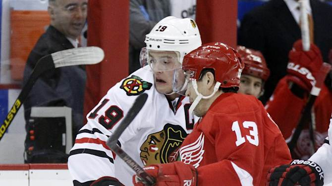 Detroit Red Wings center Pavel Datsyuk (13), of Russia, knocks Chicago Blackhawks center Jonathan Toews (19) off the puck in the first period of an NHL hockey game on Sunday, March 3, 2013, in Detroit. (AP Photo/Duane Burleson)