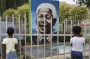 Children look through a fence at a portrait of former president Nelson Mandela in a Park in Soweto, South Africa, Thursday, March, 28, 2013. 94-year-old Mandela, the anti-apartheid leader who became South Africa's first black president, has been hit by a lung infection again and is in a hospital, the presidency said. Mandela, has become increasingly frail in recent years and has been hospitalized several times in recent months, including earlier this month when he underwent what authorities said was a scheduled medical test. The Nobel laureate is a revered figure in South Africa, which has honored his legacy of reconciliation by naming buildings and other places after him and printing his image on national banknotes. (AP Photo/Denis Farrell)