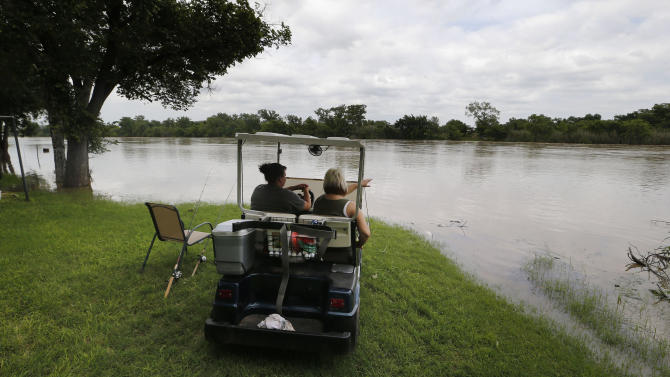 Tosha Miller and Tammie Cowden fish and watch the river rise as authorities call for an evacuation of Horseshoe Bend, Texas, because the Brazos River is expected to flood, Wednesday, May 27, 2015. (Rodger Mallison/The Fort Worth Star-Telegram via AP) MAGAZINES OUT; (FORT WORTH WEEKLY, 360 WEST)