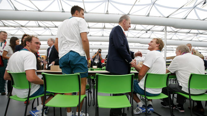 In this Monday, July 23, 2012 photo, IOC President Jacques Rogge, center, shakes hands with Australian water polo player Sam McGregor, second from right, during his visit to the Athletes' Village at the Olympic Park, in London. More than 1 million items from the athletes village and Olympics Park are on sale right here, right now, and they'll be ready for collection right after the Paralympic Games end in early September. Included are; night stands, lamps, umpire's chairs an even beanbags. (AP Photo/Jae C. Hong)