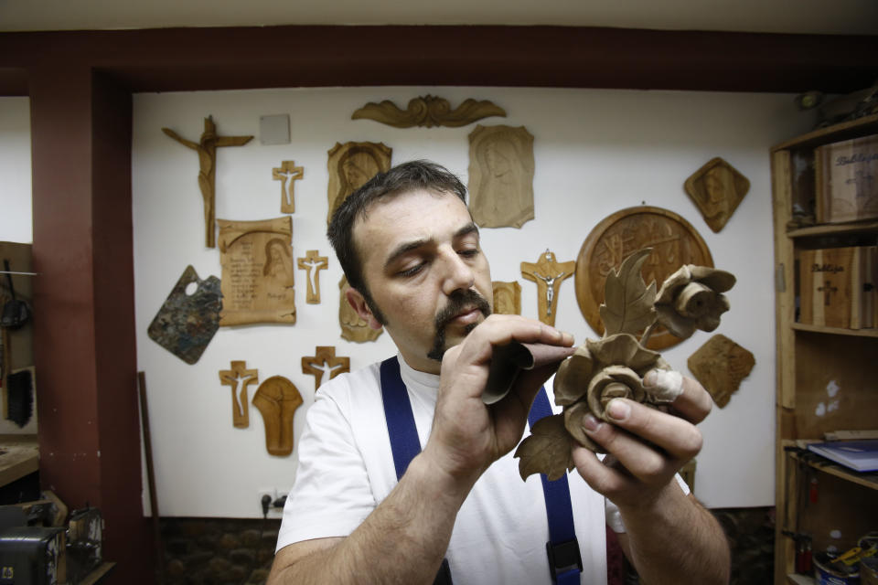 In this photo taken on Saturday, March, 28,2015 Bosnian Muslim craftsman  Edin Hajdarovac engraves decoration onto part a wooden chair in his workshop...