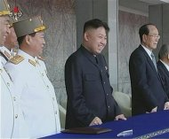 Still image of North Korean leader Kim Jong-un smiling next to Kim Yong-nam during a mass parade in Pyongyang