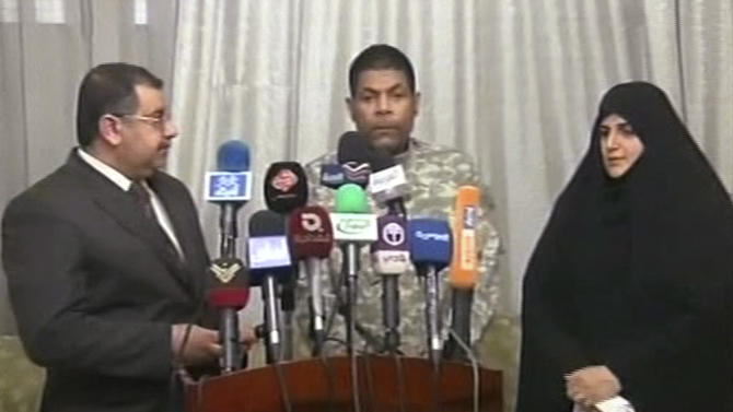 In this image taken from TV Saturday March 17, 2012, showing a man identified as Randy Michael, centre, who is purported to be an American contractor, in Baghdad, Iraq, who was handed over to the United Nations by Shiite lawmakers representing the hardline followers of anti-American cleric Muqtada al-Sadr.  The United Nations mission in Iraq confirmed Saturday that it took custody of a man who was described as a U.S. citizen, who had been held captive by an Iraqi militia group for about nine months.(AP Photo/MASAR TV) IRAQ OUT - TV OUT