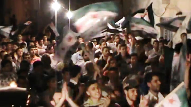 This image made from amateur video and released by the Syria media center Tuesday, May 1, 2012, purports to show Syrians chanting slogans during a demonstration in Aleppo, Syria. On Wednesday, activists north of the northern city of Aleppo said troops were engaged in intense clashes with army defectors and rebels in the village of al-Raai. An activist who identified himself by his first name Ammar said the clashes began at night and were continuing Wednesday. (AP Photo/Syria Media Center via APTN) THE ASSOCIATED PRESS CANNOT INDEPENDENTLY VERIFY THE CONTENT, DATE, LOCATION OR AUTHENTICITY OF THIS MATERIAL. TV OUT