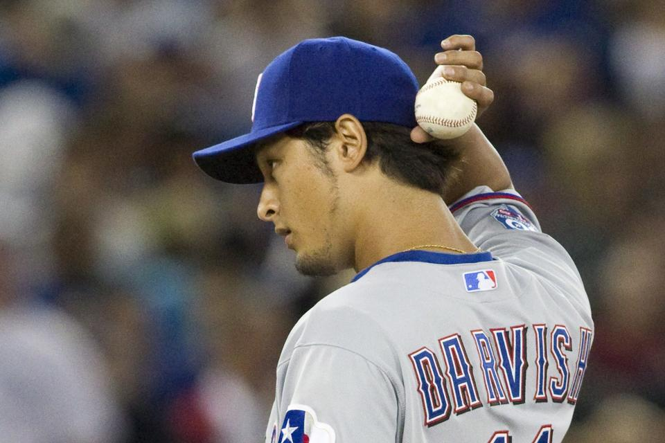 Texas Rangers pitcher Yu Darvish reacts as he works against the Toronto Blue Jays during the first inning of baseball game action in Toronto, Friday, Aug. 17 , 2012. (AP Photo/The Canadian Press, Chris Young)