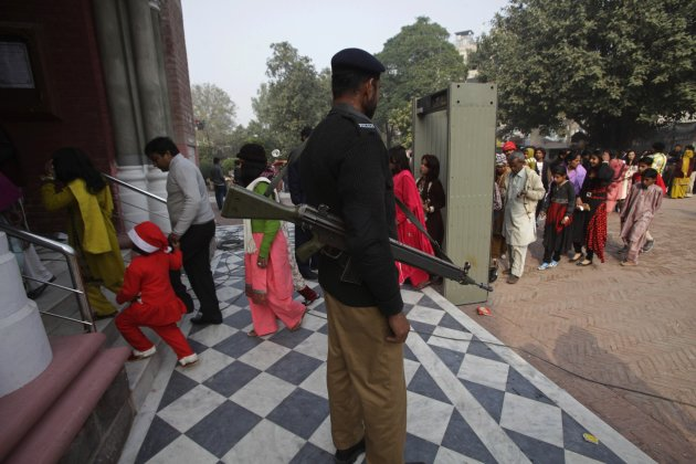 A police officer stands guard while Pakistani Christians arrive to attend mass on Christmas day in Lahore
