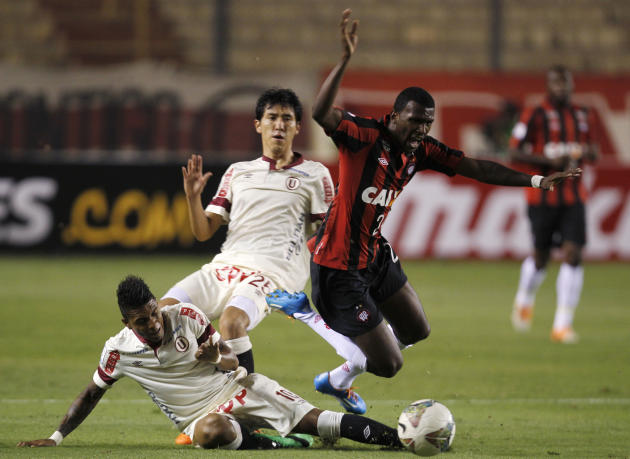 Douglas Coutinho of Brazil's Atletico Paranaense, right, fights for the ball with Alex Gomez, left, and Angel Romero, center, of  Peru's Universitario during a Copa Libertadores soccer match i