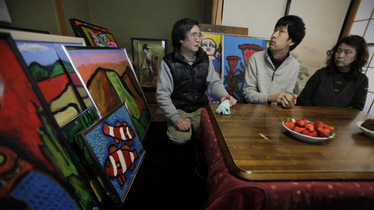 In this Saturday, Feb. 23, 2013 photo, artist Minoru Tasaki, his disabled son Asuka, center, and wife Mieko sit together with Asuka's paintings in Rikuzentakata, Iwate Prefecture, northeastern Japan. Tasaki and Asuka's works were swept away by the tsunami. For now, their work is on hold as they prepare to move from their temporary, rented hillside home to another district. (AP Photo/Junji Kurokawa)