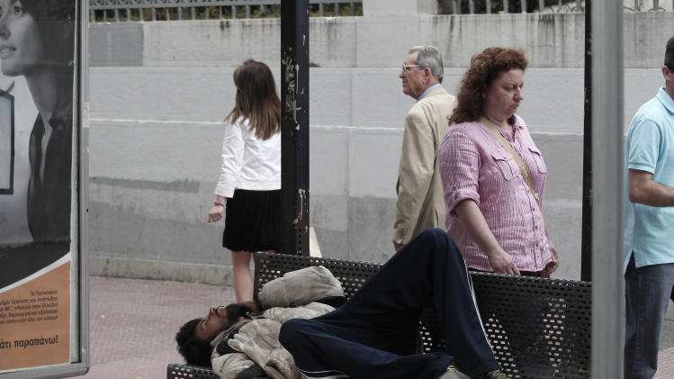 An immigrant sleeps at a bench of a bus stop  in central  Athens on Tuesday May 29, 2012. The four biggest Greek banks received 18 billion euros (22.6 billion USD) in rescue funds on May 28, 2012 to help reinforce their capital bases, a Hellenic financial stability fund source said. National Bank, the biggest Greek lender, has received 7.43 billion euros, Piraeus bank 4.7 billion, Eurobank 3.97 billion and Alpha 1.9 billion, the official said.(AP Photo/Dimitri Messinis)