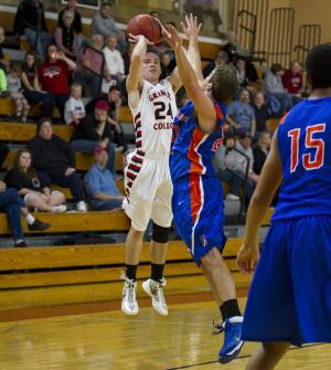 In this photo provided by Grinnell College, Grinnell College's Jack Taylor, left, takes a jump shot over Crossroads' AJ Kuhn during a Division III college basketball game on Sunday, Nov. 17, 2013, in Grinnell, Iowa. Taylor scored 109 points in Grinnell's 173-123 victory. (AP Photo/Grinnell College, Justin Hayworth)