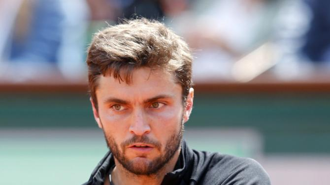 Gilles Simon of France plays a shot to compatriot Lucas Pouille during their men's singles match at the French Open tennis tournament at the Roland Garros stadium in Paris