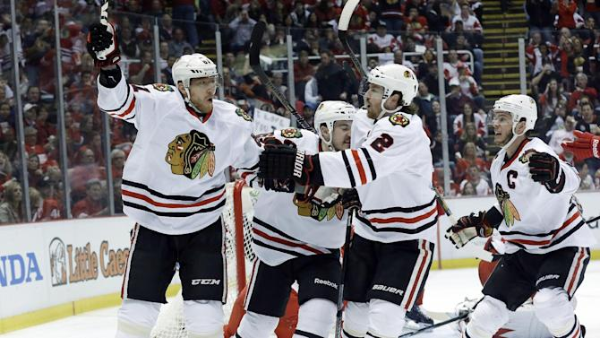 Chicago Blackhawks right wing Marian Hossa, left, of the Czech Republic, celebrates his goal against the Detroit Red Wings with Andrew Shaw, Duncan Keith (2) and Jonathan Toews (19) during the first period in Game 6 of the Western Conference semifinals in the NHL hockey Stanley Cup playoffs in Detroit, Monday, May 27, 2013. (AP Photo/Paul Sancya)