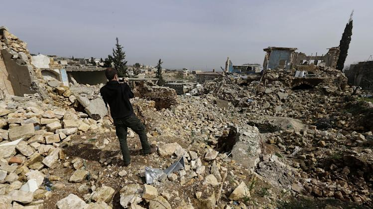 A Free Syrian army fighter films homes that were destroyed from a government airstrike, at Jabal al-Zaweya village of Sarjeh, in Idlib, Syria, Monday Feb. 25, 2013. Syria is ready to hold talks with the armed opposition trying to topple President Bashar Assad, the country's foreign minister said Monday, in the government's most advanced offer yet to try to resolve the 2-year-old civil war through negotiations. (AP Photo/Hussein Malla)