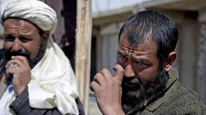 Afghan carpenter Abdullah, right, wipes his tears away as he tells his story about an Afghan special forces solider who slammed the end of his rifle into Abdullah's neck causing a fracture in his vertebrae, in Maidan Shahr, Wardak province, Afghanistan, Sunday, March 10, 2013. Afghan President Hamid Karzai, infuriated by villager reports of forced detentions and mass arrests, gave U.S. Special Forces two weeks to vacate Wardak province, located barely 30 kilometers (24 miles) from the Afghan capital of Kabul. The deadline for their withdrawal expired midnight Sunday, March 10, 2013. (AP Photo/Anja Niedringhaus)