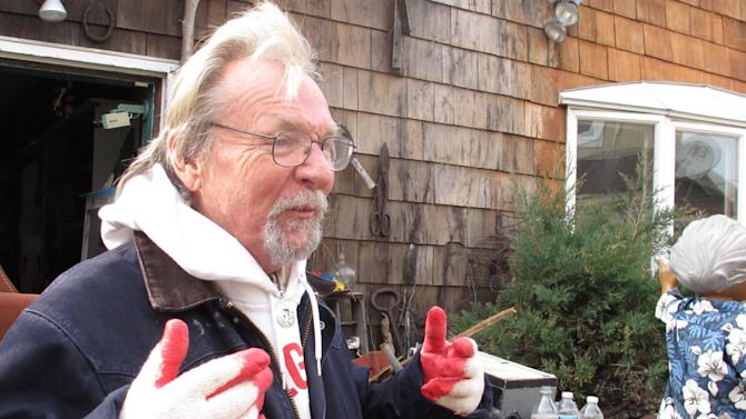 In this Friday, Nov. 16, 2012 photo, artist Kenny Goodman describes the damage from Superstorm Sandy inside his shop in the Fire Island community of Ocean Beach, N.Y. (AP Photo/Frank Eltman)