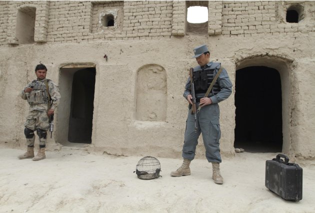 In this Sunday, March 11, 2012 photo, Afghan security forces stand guard outside a home where witnesses say Afghans were killed by a U.S. soldier in Panjwai, Kandahar province south of Kabul, Afghanis