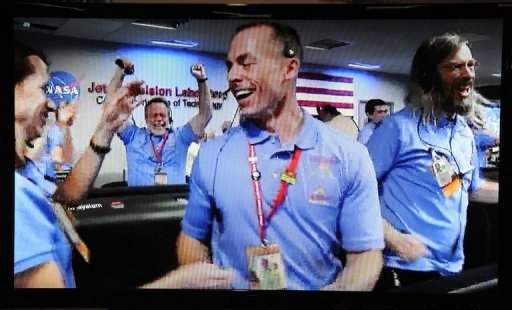 NASA Television shows the crew in the Mission Control room at the Mars Science Laboratory errupting in celebration as a successful landing on the Red Planet is confirmed on August 5, 2012, in Pasadena, California.