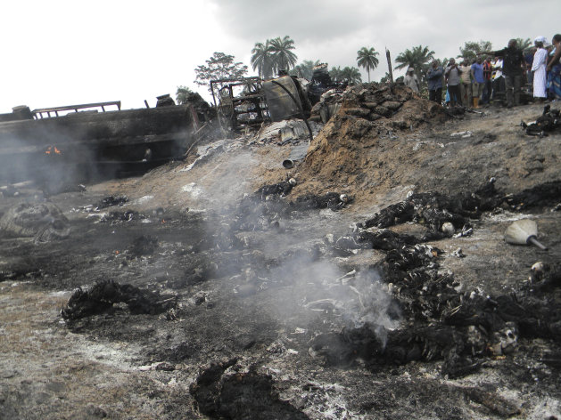 People look at charred bodies following fuel tanker explosion in Okogbe near Port Harcourt Nigeria, Thursday, July 12, 2012. A truck carrying fuel caught fire and exploded in Nigeria on Thursday after it veered off the road into a ditch, killing at least 95 people who had rushed to the scene to scoop fuel that had spilled, an official said.(AP Photo)
