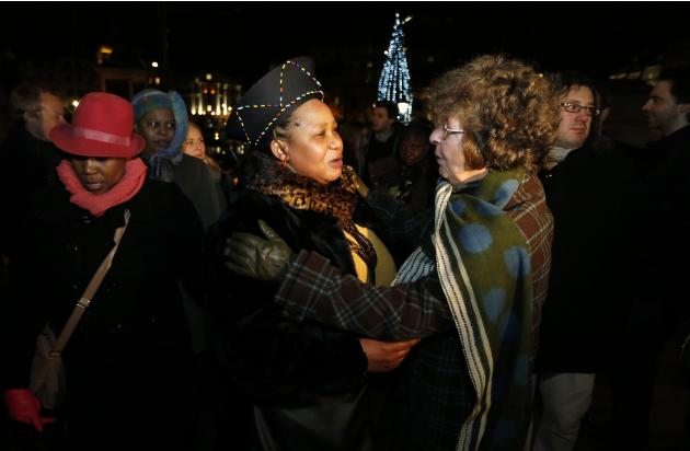 Two women embrace at a gathering in memory of Nelson Mandela outside the South African High Commission across from Trafalgar Square in London
