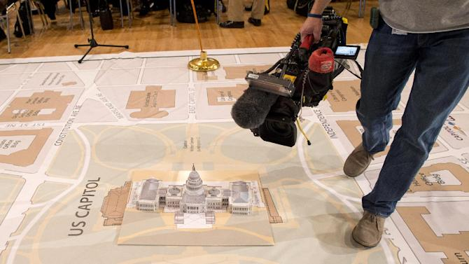 A news photographers takes photos of a model of the Capitol on a giant planning map during a media tour highlighting inaugural preparations being made by the Joint Task Force-National Capital Region for military and civilian planners , Wednesday, Dec. 12, 2012, at the DC Armory in Washington.  (AP Photo/ Evan Vucci)