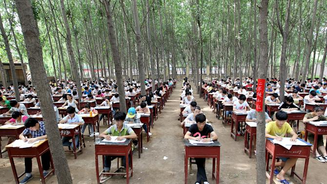 Students take term final exam among trees outside classroom building at a middle school in Xinxiang