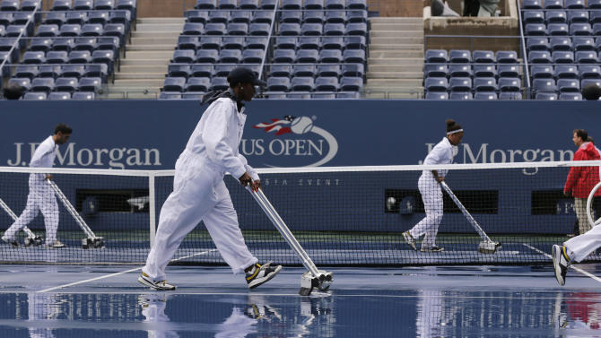 FILE - In this Sept. 8, 2012, file photo, workers clear water from the court at Arthur Ashe Stadium for a semifinal match at the 2012 US Open tennis tournament in New York. After all the rain in recent years, the first significant steps have been taken toward putting a retractable roof on Arthur Ashe Stadium; it's supposed to be ready for the 2016 U.S. Open. (AP Photo/Charles Krupa, File)