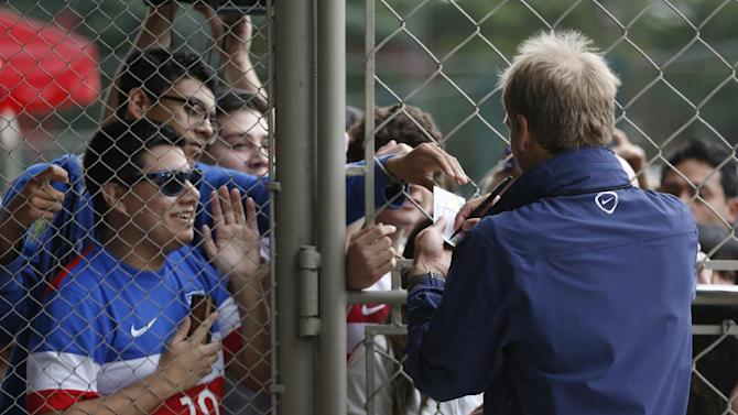 United States' head coach Juergen Klinsmann signs autographs at the Sao Paulo FC training center in Sao Paulo, Brazil, Wednesday, June 11, 2014. The U.S. will play in group G of the 2014 soccer World Cup. (AP Photo/Julio Cortez)