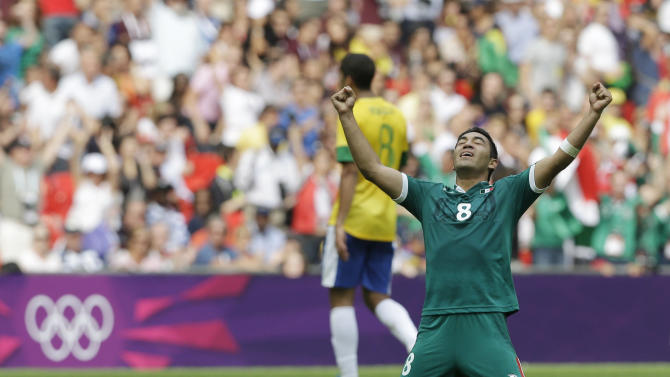 Mexico's Marco Fabian, foreground, reacts as Brazil's Romulo walks off the field during the men's soccer final at the 2012 Summer Olympics, Saturday, Aug. 11, 2012, in London. (AP Photo/Hassan Ammar)