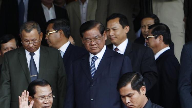 Cambodian Prime Minister Hun Sen, left, waves to officials after a meeting in Senate headquarters in Phnom Penh, Cambodia, Tuesday, July 22, 2012. Leaders of Cambodia's ruling and opposition parties say they have reached an agreement to end a political deadlock since last year's contentious election. (AP Photo/Heng Sinith)