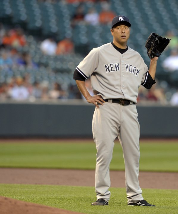 New York Yankees starting pitcher Hiroki Kuroda waits to get the ball back from at teammate after giving up a double to Baltimore Orioles batter Matt Wieters during a three-run first inning of their M
