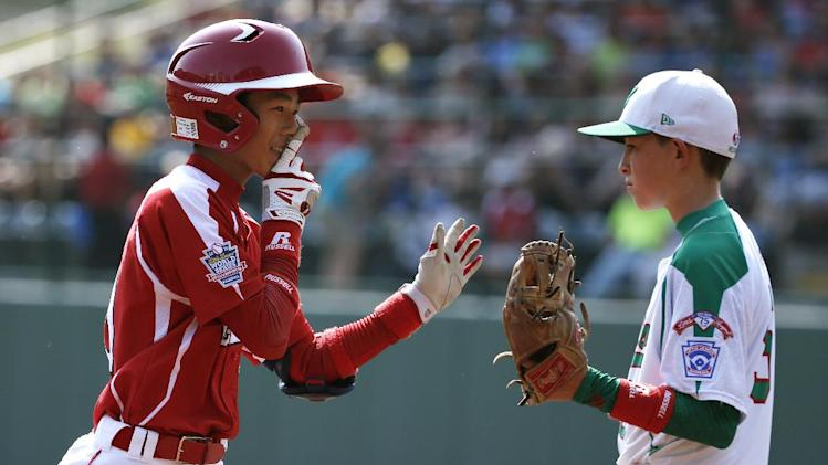 Japan's Suguru Kanamori (10) is greeted by Mexico's Rolando Reyna as he rounds third after hitting a solo home run off Mexico's Erick Vela in the first inning of an International elimination baseball game at the Little League World Series tournament in South Williamsport, Pa., Thursday, Aug. 21, 2014. (AP Photo/Gene J. Puskar