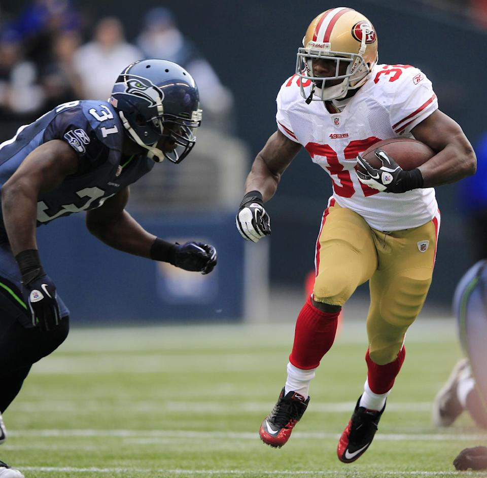 San Francisco 49ers'  Kendall Hunter (32) rushes as Seattle Seahawks'  Kam Chancellor defends in the first half of an NFL football game Saturday, Dec. 24, 2011. (AP Photo/John Froschauer)