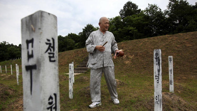 "In this Thursday, June 28, 2012 photo, Mukgai, a South Korean who goes by his Buddhist name and plans to become a monk, offers a prayer for buried North Korean and Chinese soldiers who died in the Korean War at the ""enemy cemetery,""  south of the Demilitarized Zone in Paju, South Korea. Hundreds of identical wooden grave markers poke out of the grass on the hill surrounded by rice paddies and trees, North Korea's dark mountains visible in the distance. Some are rotting; some have been knocked to the dirt; most have no names.  (AP Photo/Hye Soo Nah)"