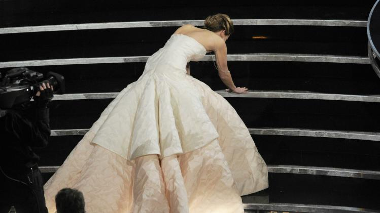 """Jennifer Lawrence stumbles as she walks on stage to accept the award for best actress in a leading role for """"Silver Linings Playbook"""" during the Oscars at the Dolby Theatre on Sunday Feb. 24, 2013, in Los Angeles.  (Photo by Chris Pizzello/Invision/AP)"""
