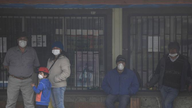 Residents wearing surgical masks to protect themselves against ash from the Calbuco volcano, look on at Curarrehue town