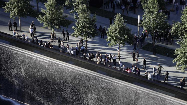 Friends and families of victims of the Sept. 11, 2001, terror attacks, look over a reflecting pool during a ceremony at the National September 11 Memorial, Tuesday, Sept. 11, 2012 in New York. As in past years, thousands are expected to gather at the World Trade Center site in New York, the Pentagon and Shanksville, Pennsylvania, to read the names of nearly 3,000 victims killed in the worst terror attack in U.S. history.  (AP Photo/Mark Lennihan)