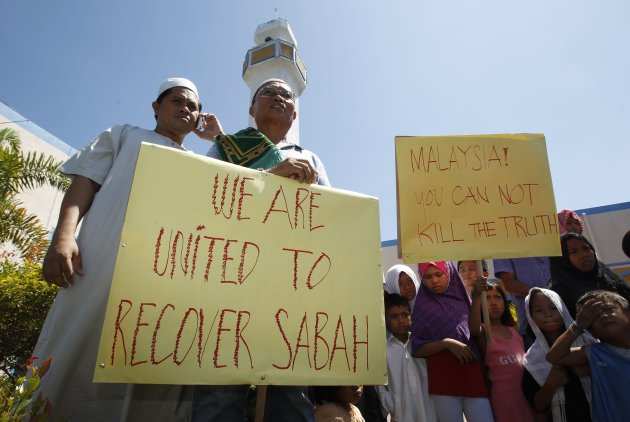 Followers of former Sultan of Sulu Jamalul Kiram III display placards while holding a brief protest in front of the Blue Mosque in Maharlika village, Taguig city, south of Manila