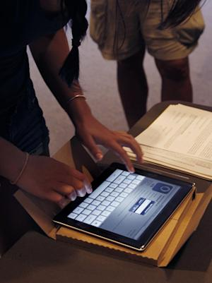 FILE - In this Aug. 23, 2011 file photo, a student unpacks her new iPad at Burlington High School in Burlington, Mass. Apple is inviting reporters to an event next Wednesday, March, 7, 2012, in San Francisco. An image on the invite showing part of an iPad screen suggests it's to announce a new model. (AP Photo/Elise Amendola, File)