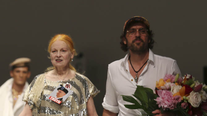 British designer Vivienne Westwood and her husband Andreas Kronthaler walk on the catwalk at the end of the men's Spring-Summer 2014 fashion show, part of the Milan Fashion Week, unveiled in Milan, Italy, Sunday, June 23, 2013. On her dress she pinned a photo of US Army soldier Bradley Manning, who was arrested in 2010 on suspicion of having made public classified material through the website WikiLeaks. (AP Photo/Luca Bruno)