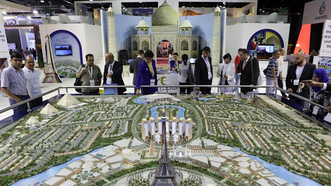 FILE - In this Wednesday, Oct. 9, 2013 file photo, Visitors watch a model for the Falconcity project during the second day of a real estate fair called Cityscape Global in Dubai, United Arab Emirates. A global property consultant said Monday there are worrying signs that Dubai could be facing another economic bubble after property prices jumped more than 22 percent last year and rents by 17 percent. (AP Photo/Kamran Jebreili, File)