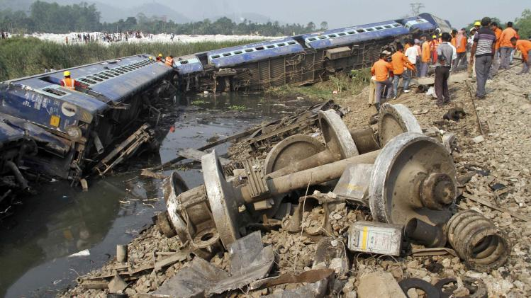 Rescue workers and onlookers stand next to derailed coaches of a passenger train in Assam