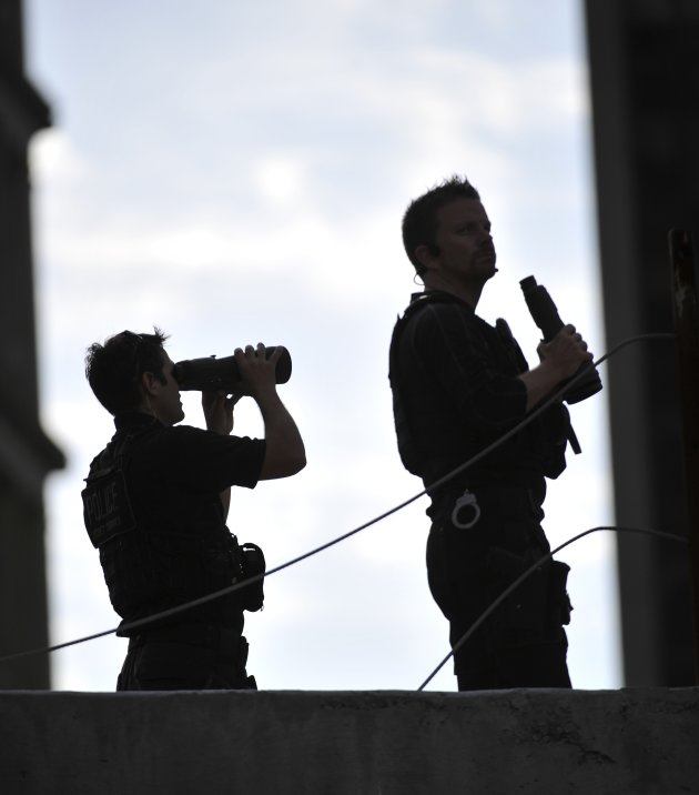 Security personnel use binoculars from their vantage point during 10th anniversary ceremonies at the site of the Sept. 11 memorial, Sunday Sept. 11, 2011, in New York. (AP Photo/Robert Deutsch, Pool)